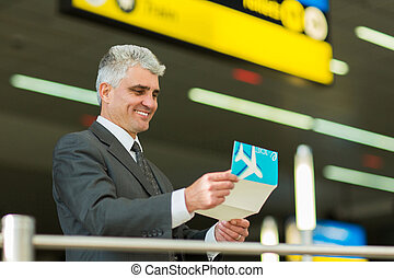 senior businessman looking at his air ticket