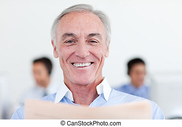 Smiling senior businessman reading