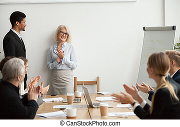 Smiling senior businesswoman boss and team clapping hands at mee