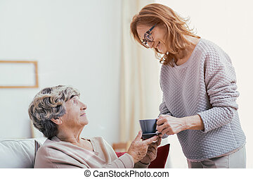 Smiling senior care assistant supporting happy elderly lady at home