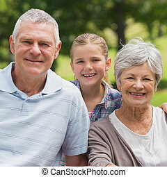 Smiling senior couple and granddaughter at park