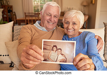 Smiling senior couple holding a photo of their youthful...