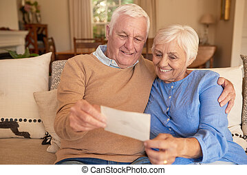 Smiling senior couple looking at old photos together at home