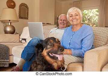 Smiling senior couple relaxing with their dog at home