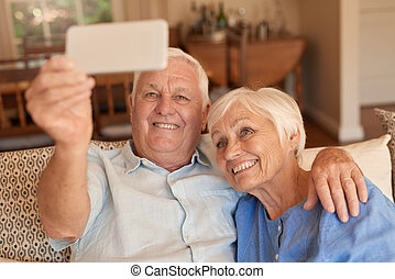 Smiling senior couple taking cellphone selfies together on...