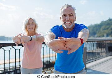 Smiling senior couple warming up together