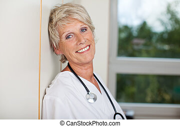 Smiling Senior Female Doctor Against Wall In Hospital