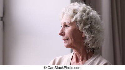 Smiling senior grandma looking through window. Happy optimistic elder 70 years old lady dreaming, thinking of good future feels relaxed. Carefree older woman enjoys well being in retirement life concept.