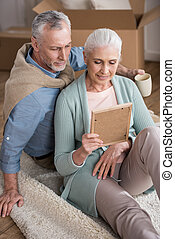 smiling senior husband and wife looking at photo frame together