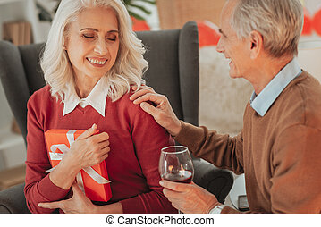 Smiling senior lady holding a gift and sitting near her husband