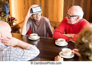 Smiling senior lady playing word-guessing game with best friends