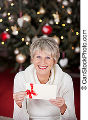 Smiling senior lady with a gift voucher