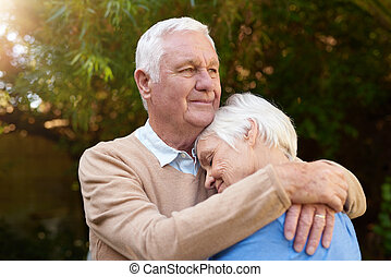 Smiling senior man affectionately hugging his wife outside