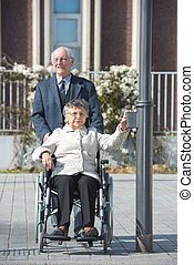 smiling senior man and his wife in a wheelchair