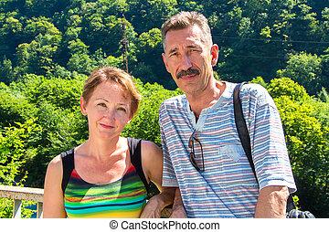 Smiling senior man and woman looking at camera