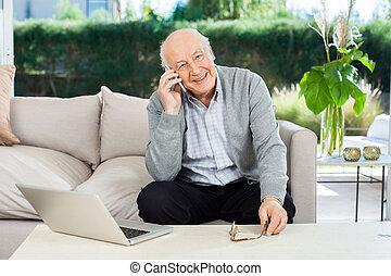 Smiling Senior Man Answering Smartphone At Nursing Home Porch