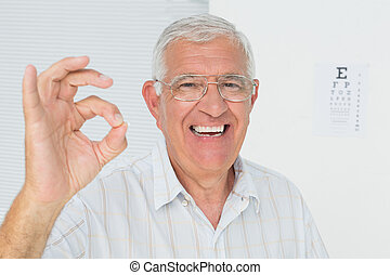 Smiling senior man gesturing ok with eye chart in background