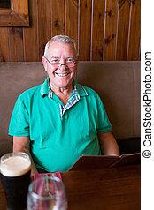 Smiling senior man holding a restaurant menu