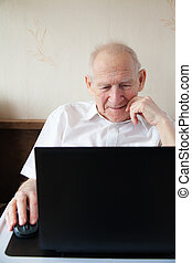 Smiling Senior Man In Front Of the Laptop