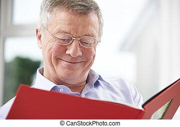 Smiling Senior Man Looking At Photo Album