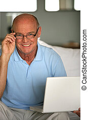 Smiling senior man on a couch with laptop