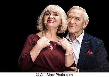 Smiling senior man putting necklace on happy wife on black