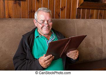 Smiling senior man reading a restaurant menu