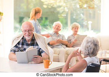 Smiling senior man reading book - Senior man reading book...