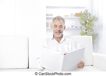 Smiling senior man reading file folder on the couch