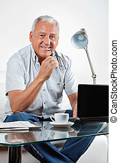 Smiling Senior Man With Laptop on Table