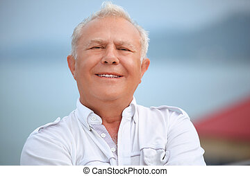 smiling senior near seacoast against mountain
