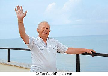 smiling senior on veranda near seacoast, lifted hand upwards