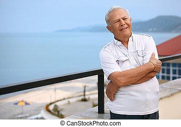 smiling senior on veranda near seacoast