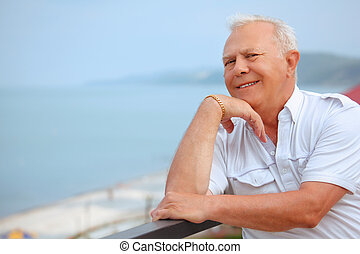 smiling senior on veranda near seacoast, lean elbows about handrail