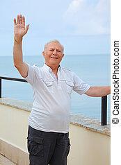 smiling senior on veranda near seacoast, lifted hand upwards, vertical portrait