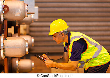 senior shipping worker inspecting machinery