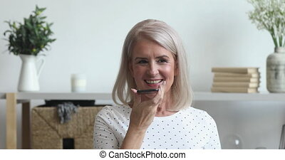 Smiling middle aged old woman hold phone speak activate virtual digital voice recognition assistant at home, happy senior lady command internet assistance record message, mobile ai technology concept
