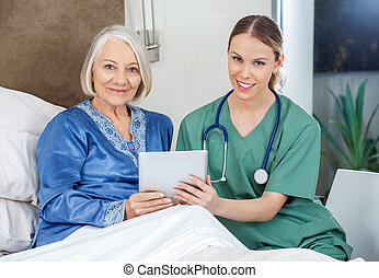 Smiling Senior Woman And Caretaker Holding Tablet PC -...
