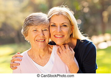 smiling senior woman and middle aged daughter outdoors closeup portrait