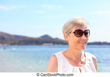 Smiling senior woman at beach. Happy elderly female in casuals is wearing sunglasses. Woman is on her summer vacation