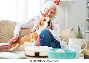Smiling Senior Woman Celebrating Birthday with Dog