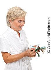 Smiling senior woman counting money