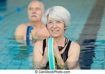 smiling senior woman doing aqua fitness