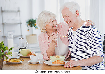 Smiling senior woman feeding husband
