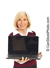Smiling senior woman holding open laptop