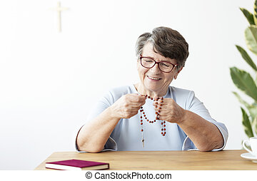 Smiling senior woman holding rosary while sitting at table with bible