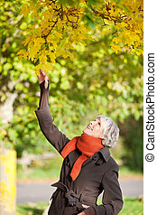 Smiling Senior Woman Holding Tree Branch