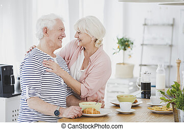 Smiling senior woman hugging husband