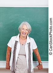 Smiling senior woman in front of a blackboard leaning on a ...