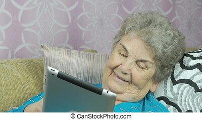 Smiling senior woman lies on at hotel room sofa